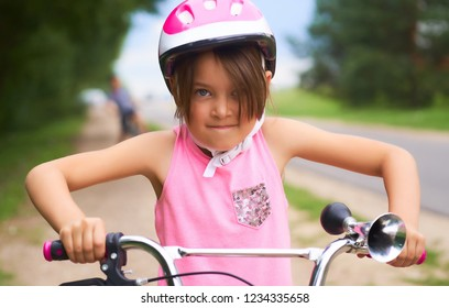 Portrait of a litte girl in a pink safety helmet driving her bike.