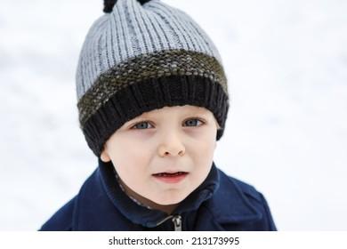 Portrait of littel boy in winter in warm hat and coat
