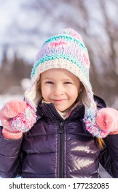 Portrait of little adorable girl in winter hat at snowy forest
