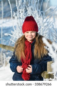 Portrait of a little adorable girl in winter hat in snow forest