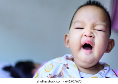 Portrait of a little adorable infant baby gape on the bed
