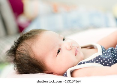 Portrait of a little adorable infant baby girl lying on the back on the pillow
