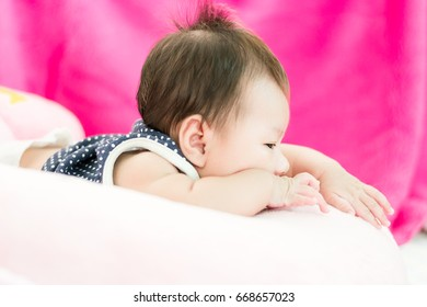 Portrait of a little adorable infant baby girl lying on the tummy on the pillow