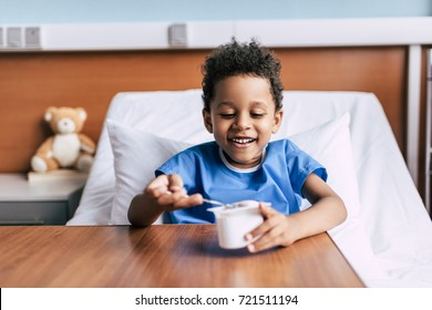 portrait of little african american boy eating yogurt while resting in hospital bed