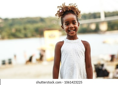 Portrait of little african american girl.She standing at the beach and smiling.