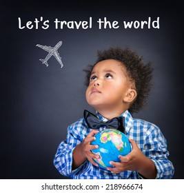Portrait of a little African American schoolboy holding in hands small globe, dreaming about traveling all over the world, happy childhood concept