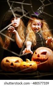 Portrait of little aggressive Halloween girls with pumpkins