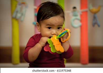 a portrait of  Little asian  boy. Cute baby boy sitting on a playmate and playing with toy by himself. Adorable eight month old child happy reach the toy. Blurred with select focus