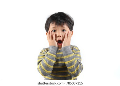 Portrait of a little Asian boy looking extremely surprised with his mouth open and hands on his face