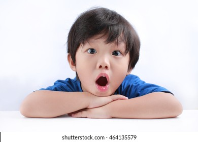 Portrait of a little Asian boy looks shocked at camera. Isolated on white background.