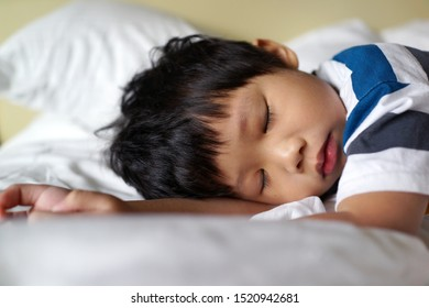 Portrait of little Asian boy sleeping in bed at home