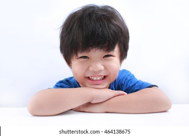 Portrait of a little Asian boy smilling at the camera as he sits at a table resting his chin on his folded arms. Isolated on white