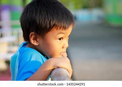 Portrait of a little Asian child boy feeling sad. He standing at the playground and hands holding a iron fence. Expression and emotions of kid concept.