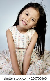Portrait of Little Asian child is smiling on gray background .