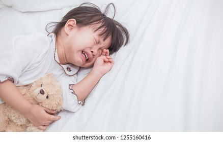 Portrait of little asian crying girl with little rolling tears weeping emotion, Closeup young girl hurt in pain crying in white bed with copy space. Lonely depress stress angry unhappy concept