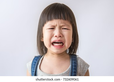 Portrait of little asian crying girl with little rolling tears weeping emotion, hurt in pain fit drops cheek