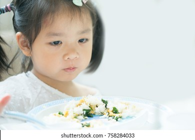 Portrait of Little asian girl child with no appetite in front of the meal.Concept of loss of appetite
