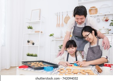 Portrait of little asian girl and her parents baking cooking cake and cookies in the kitchen. Happy asian family and mother's day, healthcare food cooking concept