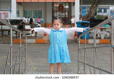 Portrait of little Asian girl in school uniform with stretch arms and looking straight.