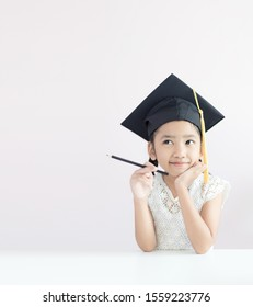Portrait little Asian girl is wearing graduate hat holding pencil sitting thinking something and smile with happiness select focus shallow depth of field with copy space for education concept
