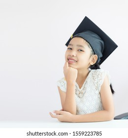 Portrait little Asian girl is wearing graduate hat and smile with happiness select focus shallow depth of field with copy space for education concept