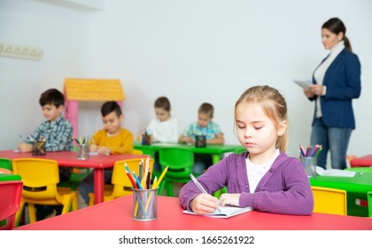Portrait of little assiduous girl with pen and notebook at lesson in elementary school