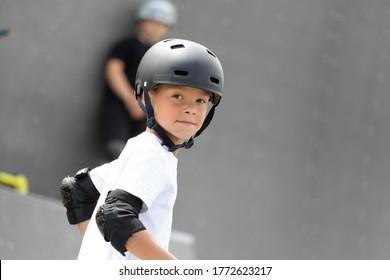Porträt eines kleinen Athleten. Ein süßer kleiner Junge fährt einen Roller in einem Skatepark. Ein junger Anfänger verbringt Freizeit im Extremsport.