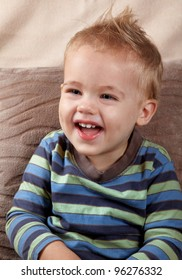 Portrait of a little baby boy laughing outloud. Indoor shot.