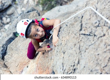 Portrait of little Baby Girl climbing vertical natural rock doing difficult move top view