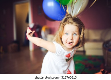 portrait of little baby girl at home on the day of birth in a dress with colorful balls smiles and laughs