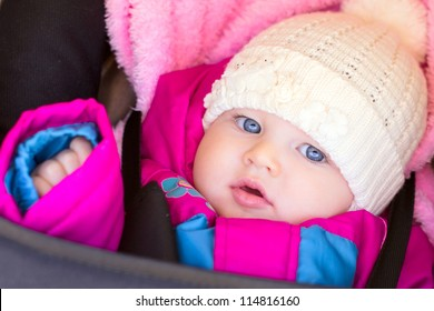 portrait of little baby girl in purple rose jacket and hat