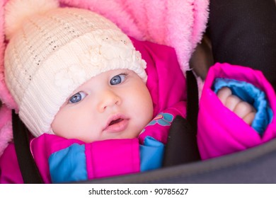 portrait of little baby girl in purple rose jaket and hat