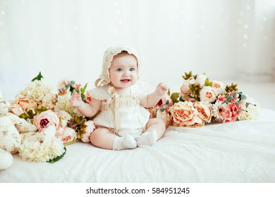 Portrait of little baby girl in white vintage home with flowers