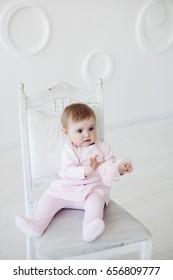 Portrait of little baby girl in white vintage studio in pink dress
