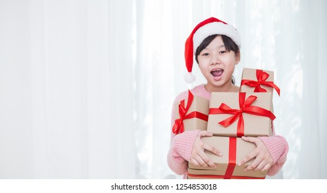 Portrait of little beautiful asian Japanese teenage girl wearing red hat holding big gift box with copy space, christmas boxing day open present concept panoramic banner