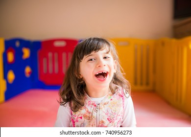 Portrait of little beautiful disabled girl who sitting in the game room and smiling