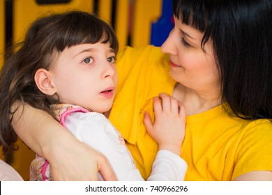 Portrait of little beautiful disabled girl who lying in her mother's arms in the room