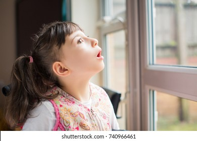 Portrait of little beautiful disabled girl who looking in the window indoors