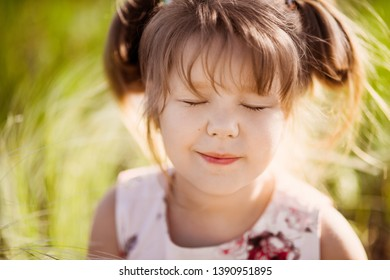 portrait of a little beautiful girl child on the background of a blooming park in spring, summer flower mood.