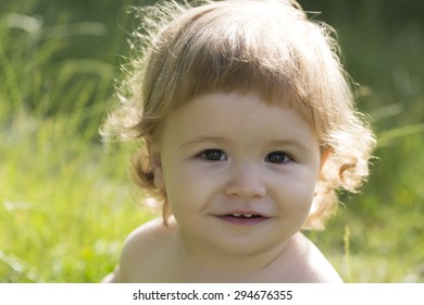 Portrait of little beautiful happy child boy with blonde curly hair smiling and sitting on fresh green grass outdoor on natural background, horizontal picture