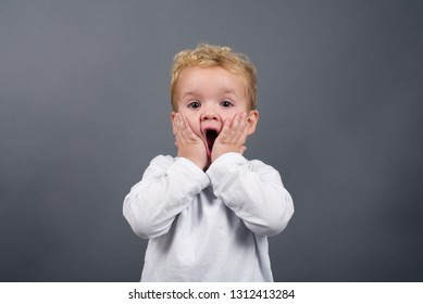 Portrait of little blond boy holding hands on face, screaming with opened mouth and crazy expression. Surprised or shocked face. Exclaiming: Wow, I can't believe this.