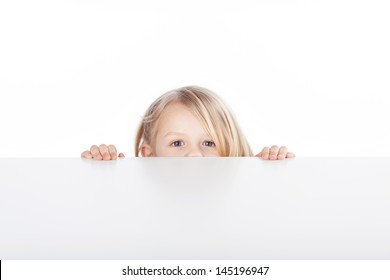 Portrait of little blond girl peeking over table isolated over white background