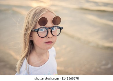 Portrait of little blond girl wearing goggles at the beach
