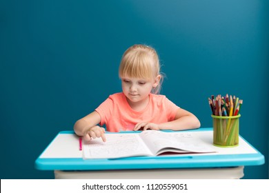 Portrait of little blonde girl is sitting at the table and paints. Schoolkid is doing her homework in classroom at school or at home. She shows finger on letters or numbers