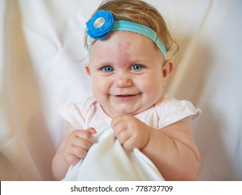 Portrait of a little blonde girl sitting with a blue bandage around her head