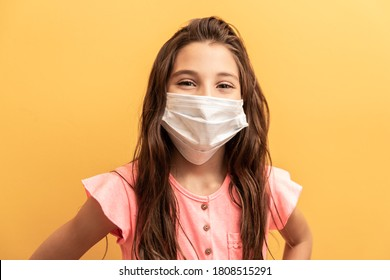 Portrait of little blonder girl with medical face mask looking at camera. Child wearing protective mask from virus . Coronavirus and pandemic concept.