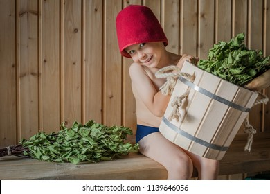 Portrait of a little boy of 5 years wrapped in a towel at preschool age, sitting in a sauna and having fun with a bucket and a birch broom in a Russian bath.