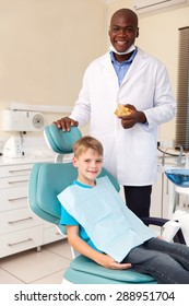 portrait of little boy and african american dentist in office