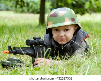 Portrait of little boy in army camouflage with toy gun outdoor