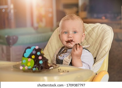 Portrait of a little boy with a birthday cake. Birthday at home alone.Chocolate-smeared face. No guests.